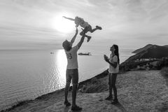 Dad throws his son in the air, and mom looks at them on the mountain with seascape. BW.  Royalty Free Stock Images