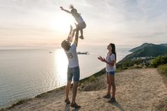 Dad throws his son in the air, and mom looks at them on the mountain with seascape. Family trip. Dad throws his son in the air, and mom looks at them on the royalty free stock photo