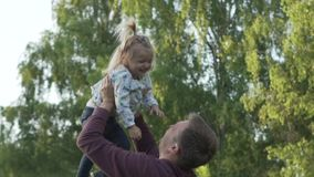 Dad throws the little girl up. Slow motion stock video footage