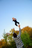 Dad throws son in autumn forest Royalty Free Stock Images