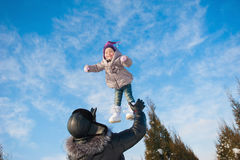 Dad throws up baby daughter in winter against the blue sky, lifestyle, winter holidays Royalty Free Stock Image