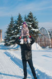 Dad throws up baby daughter in winter against the blue sky, lifestyle, winter holidays Royalty Free Stock Photography