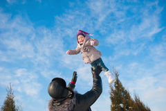 Dad throws up baby daughter in winter against the blue sky, lifestyle, winter holidays Royalty Free Stock Photos