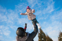 Dad throws up baby daughter in winter against the blue sky, lifestyle, winter holidays Stock Images