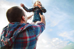 Dad throws up the girl. In the sky Stock Images