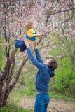 Dad throws up his son in a garden stock photo