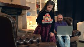 Dad is too busy to play with his pretty daughter working on computer. She has a toy castle in her hand. They sitting near the fireplace at home stock video footage
