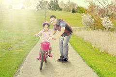 Dad trains his daughter to ride a bike Royalty Free Stock Images