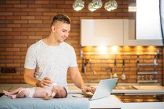 Dad trying to work while standing with his newborn babe in home office interior. Handsome overworked guy with his child crying on office table royalty free stock image