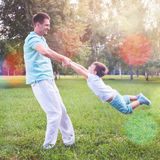 Dad turns child holding hands outdoor. Family. Father spinning his son. Happy funny people. Summer. Emotions. Childhood stock images