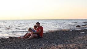 Dad with two boys sitting on a beach with sons sea. Watching the sunset stock footage