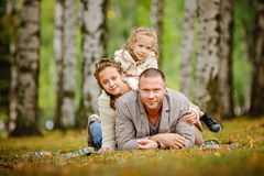 Dad and two charming sisters in the same curly beige knitted sweater, family, lie on a striped rug and a smile on the background royalty free stock image