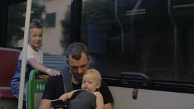 Dad with two children on the bus. Father using smart phone during the evening bus ride with elder son and one year old baby daughter stock video