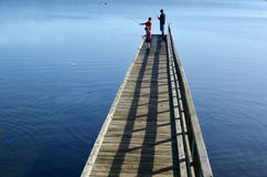 Dad and two children fishing from a pier Royalty Free Stock Photos