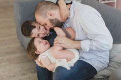 Dad and two children have a fun at home. stock photo