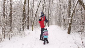 Dad with two children playing in a winter forest. Winter holidays stock footage