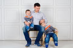 Dad with two children on his knees sitting on the chair in front of white wall. Lifestyle. Children in identical sweaters. Dad with two children sitting on chair Stock Images