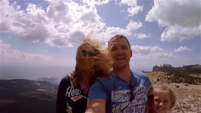 Dad and two daughters make selfie video from top of mountain. Everyone smiles and peeps. Weather is warm and sunny stock video