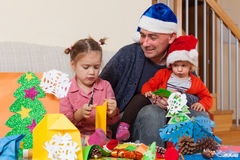 Dad with two daughters making crafts stock image