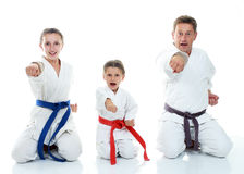 Dad with two daughters sitting in a ritual pose karate and beat his fist Royalty Free Stock Images