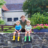 Dad and two little kid boys sitting together on stone bridge. Young dad and two little kid boys sitting together on stone bridge in european village. Happy Royalty Free Stock Photo