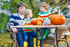 Dad and two little sons making jack-o-lantern for halloween in a Stock Image