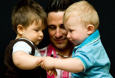 Dad with two sons. Portrait of a young handsome dad with two baby sons isolated on black background Stock Image