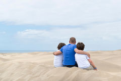 Dad and two sons. Embracing sitting on a dune and looking into the distance royalty free stock photos