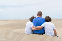 Dad and two sons. Embracing sitting on a dune and looking into the distance royalty free stock images
