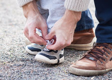 Dad tying shoelaces child. Dad tying the laces on a child sneakers Royalty Free Stock Photo