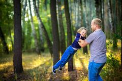 Dad walks in the park with his beloved daughter at sunset, throws up on his hands royalty free stock images