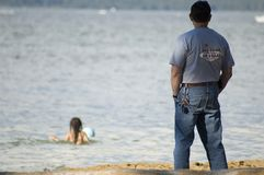 Dad watching child in sea. Rear view of dad or father watching child swim in sea Stock Image