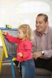 Dad watching daughter drawing. Smiling dad watching small daughter drawing on board at home royalty free stock photo