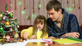 Dad is watching a daughter element sticks to the New Year hand-made article stock video footage