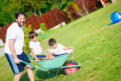 Dad in white driving his boys on the wheelbarrow Stock Images