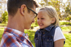 Dad and young daughter pulling faces at each other in a park Royalty Free Stock Photography