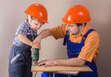 Dad with young son in protective helmet working jigsaw Royalty Free Stock Photography