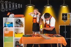 Dad and young son are working with a drill in the workshop. stock photo