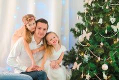 Dada feliz con los niños cerca del árbol de navidad el víspera de Navidad Fotos de archivo libres de regalías