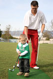 Daddy. Father and son practising on the golf driving range Royalty Free Stock Photos