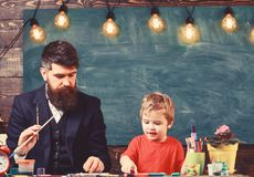 Daddy artist teaching his son how to paint. Blond kid learning to draw.  royalty free stock photos