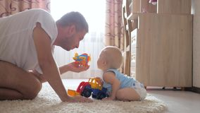 Daddy with baby boy playing with toy cars at home.