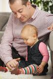 Daddy with baby girl. Daddy sitting together with baby girl on living room floor royalty free stock photo