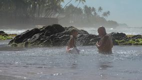 Daddy and boy have fun splashing water in tranquil ocean