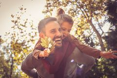 Daddy care me on piggyback. On the move. Daddy care me on piggyback. Smiling young father with his daughter royalty free stock photos
