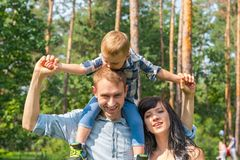 Daddy carries his son on his shoulders, mom laughs next to them. Family resting in the park in sunny day Stock Image