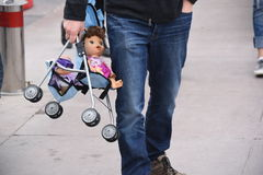 Daddy Carry My Doll. Man carrying a doll and stroller walking with hand in pocket Royalty Free Stock Photos