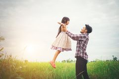 Daddy carrying his daughter with nature and sunlight, enjoyment. Family Stock Photos