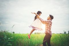 Daddy carrying his daughter with nature and sunlight, enjoyment. Family Stock Photography