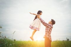 Daddy carrying his daughter with nature and sunlight, enjoyment. Family background Royalty Free Stock Images